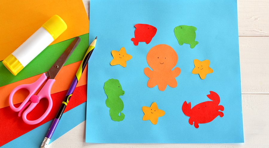 Paper sea animals on blue card. Children applique pattern. Children application. Glue stick, scissors, pencil, colored paper. Preschool and kindergarten paper crafts. DIY project.Kindergarten activity