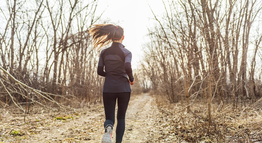 female athlete runner running in autumn nature outdoors on forest trail path in beautiful sunny sunlight fall cold weather. Unrecognizable woman in activewear tights jogging away view from behind.