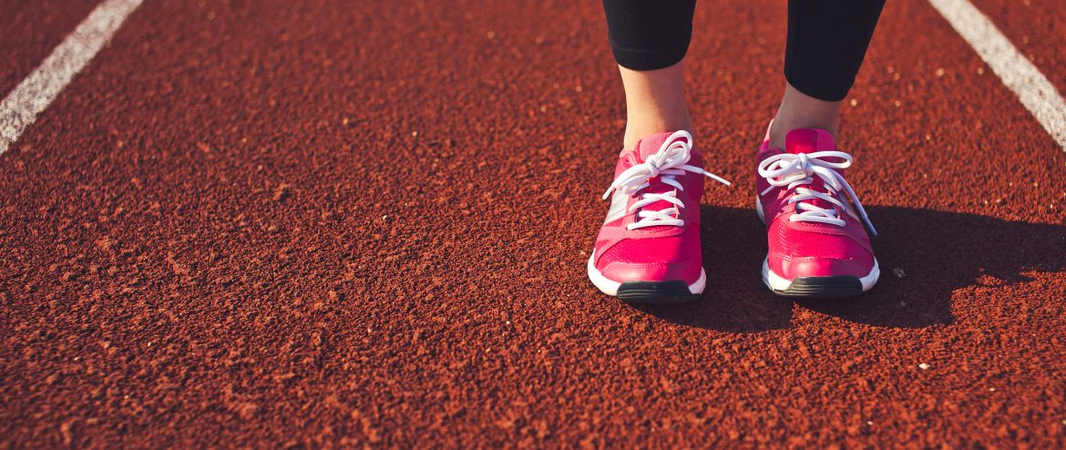 One woman standing on a running path of a stadium ready for run. Calf and feet front view. Wearing sneakers. Red running track with lines on a background. Copy space