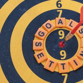 Words goals setting and dart target arrow on the bullseye of dartboard Smart goal target success business investment financial strategy concept Business abstract background
